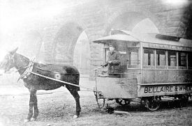 mule pulling trolley-like car with Bellaire& Wheeling on the side; in front of the Wheeling Stone Viaduct